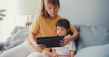 felice allegra famiglia asia mamma e bambino carino che utilizza tablet digitale interesse cartone animato e guardare film divertirsi rilassarsi sul divano nel soggiorno a casa. passare del tempo insieme, quarantena per il coronavirus. foto