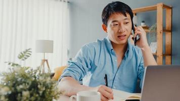freelance asia guy abbigliamento casual utilizzando laptop parlare al cellulare nel soggiorno di casa. lavoro da casa, lavoro a distanza, istruzione a distanza, distanziamento sociale, quarantena per la prevenzione del virus corona. foto