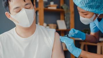 giovane infermiera asiatica che somministra vaccino antivirus covid-19 o antinfluenzale sparato a un paziente di sesso maschile che indossa una maschera protettiva dalla malattia virale sedersi sul divano nel soggiorno di casa. concetto di vaccinazione. foto