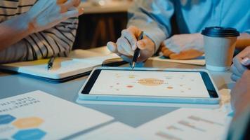 asia uomini d'affari riunione piano analisi statistiche brainstorming e intestazione del team tenere tablet punto grafico grafico e dipendente prendere nota nella moderna notte dell'ufficio a casa. concetto di successo della strategia finanziaria. foto