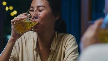 gruppo di turisti felici giovani amici asiatici che bevono alcolici o birra artigianale e fanno festa in un night club al khao san road. viaggiatore zaino in spalla asia persone viaggiano a bangkok, thailandia. foto