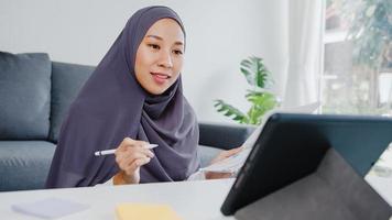 asia musulmana signora indossare foulard uso casuale tablet parlare con i colleghi del rapporto di vendita in videochiamata in conferenza mentre si lavora da casa in soggiorno. distanziamento sociale, quarantena per il virus corona. foto