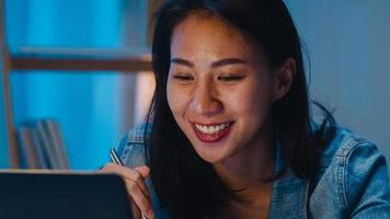 asia donne d'affari intelligenti freelance che mangiano noodles istantanei mentre lavorano al laptop nel soggiorno di casa di notte. la giovane ragazza asiatica felice che si siede sulla scrivania fa gli straordinari, godetevi il tempo di relax. foto