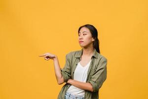 la giovane donna asiatica mostra qualcosa di straordinario nello spazio vuoto con espressione negativa, urla eccitate, pianto arrabbiato emotivo in abbigliamento casual isolato su sfondo giallo. concetto di espressione facciale. foto