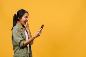 giovane donna asiatica che usa il telefono con un'espressione positiva, sorride ampiamente, vestita con abiti casual sentendosi felici e in piedi isolato su sfondo giallo. felice adorabile donna felice esulta successo. foto