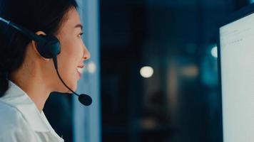 millennial asia giovane agente di call center o dirigente del servizio di assistenza clienti che utilizza computer e microfono auricolare che lavora supporto tecnico in ufficio a tarda notte. telemarketing o concetto di lavoro di vendita. foto