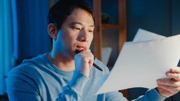 uomo d'affari freelance asiatico focus tipo di lavoro su computer portatile occupato con pieno di documenti cartacei sulla scrivania in soggiorno a casa gli straordinari di notte, lavoro da casa durante il concetto di pandemia covid-19. foto