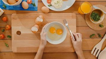 mani della giovane donna asiatica chef sbattere l'uovo in una ciotola di ceramica cucinare frittata con verdure su tavola di legno sul tavolo della cucina in casa. stile di vita sano mangiare e panetteria tradizionale. colpo di vista dall'alto. foto