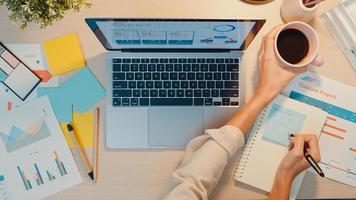 vista dall'alto della giovane donna d'affari asia freelance focus sul laptop scrivere foglio di lavoro grafico finanziario grafico del conto piano di mercato in ufficio notte. lavorare da casa, da remoto, concetto di coronavirus per l'istruzione a distanza foto