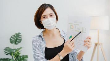 asia donna d'affari indossare maschera facciale distanza sociale in situazione per la prevenzione dei virus guardando la presentazione della fotocamera al collega sul piano nel lavoro di videochiamata in ufficio. stile di vita dopo il virus corona. foto