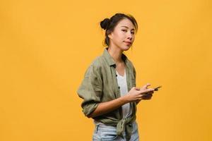 sorpresa giovane signora asiatica che utilizza il telefono cellulare con espressione positiva, sorride ampiamente, vestita con abiti casual e guardando la telecamera su sfondo giallo. felice adorabile donna felice esulta successo. foto