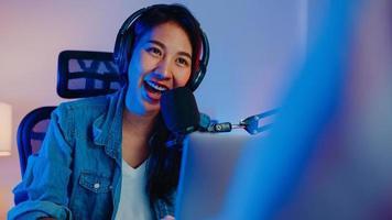 felice asia ragazza host registrare podcast utilizzare microfono indossare cuffie con laptop intervista ospite conversazione per contenuti nel suo studio di casa di notte. concetto di apparecchiature audio. concetto di creatore di contenuti. foto