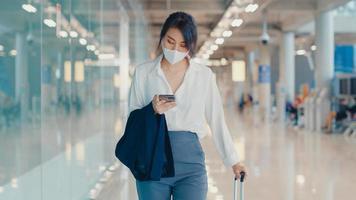 la ragazza d'affari asiatica usa lo smartphone per il check-in della carta d'imbarco a piedi con i bagagli al terminal del volo interno all'aeroporto. pandemia di covid per pendolari d'affari, concetto di distanza sociale di viaggio d'affari. foto