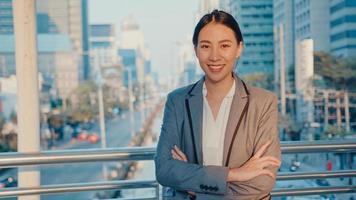 successo giovane donna d'affari asia in abiti da ufficio moda sorridente e guardando la fotocamera mentre felice in piedi da solo all'aperto nella città moderna urbana al mattino. concetto di affari in movimento. foto