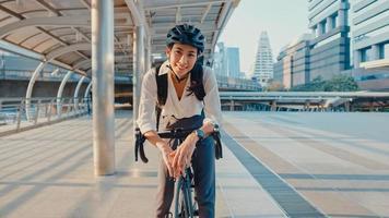 donna d'affari asiatica va a lavorare in ufficio e sorridente indossa lo zaino guarda la macchina fotografica con la bicicletta sulla strada intorno all'edificio in una città. pendolarismo in bicicletta, pendolarismo in bicicletta, concetto di pendolare aziendale. foto