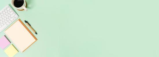 foto piatta creativa della scrivania dell'area di lavoro. scrivania da ufficio vista dall'alto con tastiera e taccuino nero mockup aperto su sfondo di colore verde pastello. vista dall'alto mock up con la fotografia dello spazio di copia.