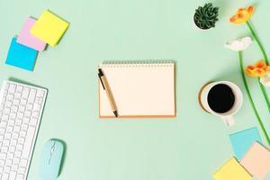 foto piatta creativa della scrivania dell'area di lavoro. scrivania da ufficio vista dall'alto con tastiera, mouse e taccuino nero mockup aperto su sfondo di colore verde pastello. vista dall'alto mock up con la fotografia dello spazio di copia.
