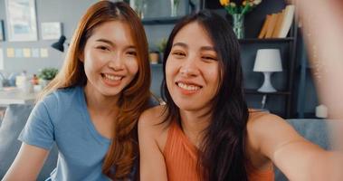 donne asiatiche adolescenti che si sentono selfie sorridenti felici e guardano la telecamera mentre si rilassano nel soggiorno di casa. Videochiamata allegra delle signore del compagno di stanza con l'amico e la famiglia, concetto di stile di vita della donna a casa. foto