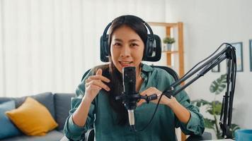 felice ragazza asiatica registra un podcast con cuffie e microfono guarda la telecamera parlare e riposati nella sua stanza. il podcaster femminile crea podcast audio dal suo studio di casa, resta al concetto di casa. foto
