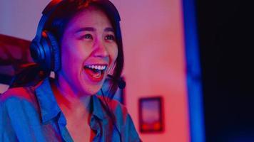 primo piano viso felice asia ragazza professionale giocatore indossare cuffie concorrenza giocare a videogiochi luce al neon computer nel soggiorno a casa. gioco in streaming di esport online, concetto di attività di quarantena domestica. foto