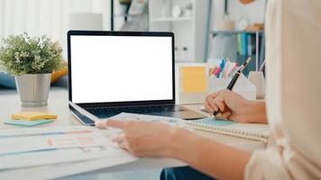 la giovane donna d'affari asiatica usa lo smartphone con lo schermo bianco vuoto finto display per il testo pubblicitario mentre lavora in modo intelligente da casa in soggiorno. tecnologia chiave di crominanza, concetto di design di marketing. foto