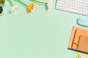 spazio di lavoro minimo - foto creativa piatta della scrivania dell'area di lavoro. scrivania da ufficio vista dall'alto con tastiera, mouse e notebook su sfondo di colore verde pastello. vista dall'alto con spazio di copia, fotografia piatta.