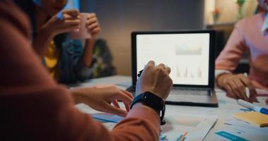millennial asia persone riunione strategica presentazione brainstorming idee su nuove scartoffie progetto colleghi che lavorano insieme pianificare strategia di successo godere del lavoro di squadra in un piccolo ufficio notturno moderno. foto