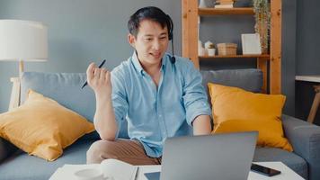 il giovane uomo d'affari asiatico indossa le cuffie utilizzando il laptop parla con i colleghi del piano in videochiamata mentre lavora da casa in soggiorno. autoisolamento, distanziamento sociale, quarantena per prevenzione covid. foto