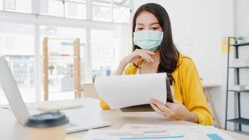 imprenditrice asiatica imprenditrice che indossa una maschera medica per il distanziamento sociale in una nuova situazione normale per la prevenzione dei virus mentre si utilizza il laptop al lavoro in ufficio. stile di vita dopo il virus corona. foto