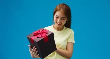giovane ragazza asiatica sorriso e tenendo aperta la casella presente isolato su sfondo blu. copia spazio per inserire un testo, un messaggio per la pubblicità. area pubblicitaria, mockup di contenuti promozionali. foto