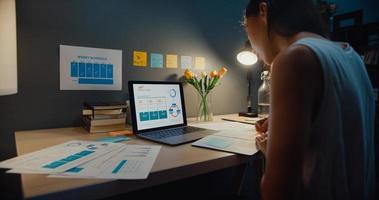 giovane asia business lady freelance focus sul laptop scrivere foglio di lavoro finanza grafico conto grafico piano di mercato a casa notte. lavorare da casa, da remoto, quarantena a distanza sociale per il concetto di coronavirus. foto