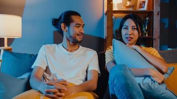 coppia romantica asia uomo e donna sorridono e ridono sdraiati sul divano nel soggiorno di notte guardano film comici in televisione insieme a casa. stile di vita familiare della coppia sposata, concetto di soggiorno a casa. foto