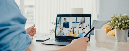 giovane uomo d'affari asiatico che utilizza laptop parla con i colleghi del piano in videochiamata riunione lavoro da casa in soggiorno. autoisolamento, distanza sociale, sfondo banner panoramico con spazio di copia. foto