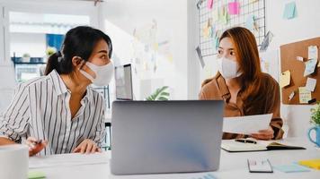 uomini d'affari asiatici che utilizzano la presentazione del computer incontrano idee di brainstorming sui nuovi colleghi di progetto e indossano una maschera protettiva per il viso nel nuovo ufficio normale. stile di vita e lavoro dopo il coronavirus. foto