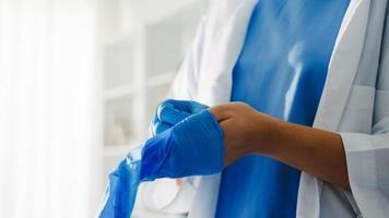 giovane donna asiatica medico o infermiere chirurgo che si prepara per l'operazione chirurgica e indossa guanti per le mani presso la clinica sanitaria o l'ufficio ospedaliero. distanziamento sociale, quarantena per coronavirus. foto