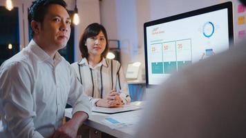gruppo di uomo d'affari asiatico e donna d'affari che utilizza computer presentazione e comunicazione incontro brainstorming idee su nuovi colleghi di progetto piano di lavoro strategia di successo in ufficio notturno. foto