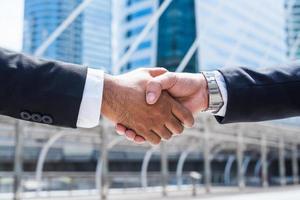 due uomini d'affari che si stringono la mano foto