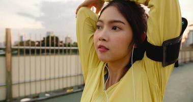 bella giovane donna atleta asiatica si esercita utilizzando lo smartphone per ascoltare la musica durante la corsa in ambiente urbano. ragazza adolescente coreana che indossa abiti sportivi sul ponte pedonale al mattino presto. foto