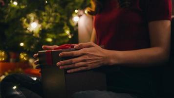 giovane donna asiatica che si diverte ad aprire la scatola regalo di Natale vicino all'albero di Natale decorato con ornamenti nel soggiorno di casa. buona notte di natale e felice anno nuovo festa delle vacanze. foto
