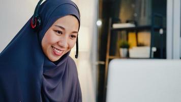 asia signora musulmana indossare cuffie guardare webinar ascoltare corso online comunicare tramite videochiamata in conferenza di notte ufficio a casa. lavoro a distanza da casa, distanza sociale, quarantena per virus corona. foto