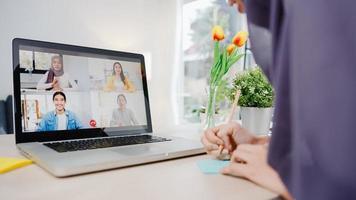 asia imprenditrice musulmana che utilizza laptop parla con un collega del piano tramite videochiamata brainstorming riunione online mentre lavora in remoto da casa in soggiorno. distanziamento sociale, quarantena per il virus corona foto