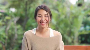donna asiatica che si sente felice sorridente e guarda la telecamera mentre si rilassa sul tavolo in giardino a casa al mattino. le donne di stile di vita si rilassano a casa concetto. foto