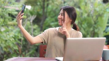 donna asiatica che utilizza il post selfie del telefono cellulare nei social media, la donna si rilassa sentendosi felice mostrando le borse della spesa seduta sul tavolo in giardino al mattino. le donne di stile di vita si rilassano a casa concetto. foto