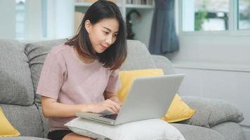 giovane donna asiatica freelance d'affari che lavora al computer portatile controllando i social media mentre è sdraiata sul divano quando si rilassa nel soggiorno di casa. stile di vita latino e donne ispaniche di etnia al concetto di casa. foto