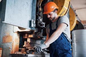 ritratto di un giovane lavoratore con un elmetto in un grande impianto di lavorazione dei metalli. l'ingegnere serve le macchine e produce parti per apparecchiature a gas foto