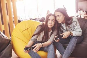 sorelle gemelle giocano sulla console. le ragazze tengono i joystick in mano e si divertono foto