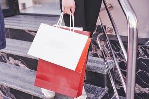Close up giovane donna che porta le borse della spesa mentre si cammina sulle scale dopo aver visitato i negozi foto