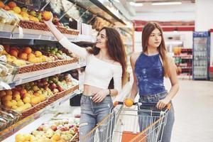 due donne che scelgono i bioprodotti producono in un supermercato con la frutta della lista della spesa. foto