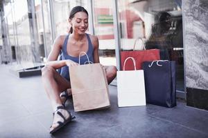 la bella ragazza si siede con le borse della spesa per strada ed è felice con i suoi nuovi vestiti foto