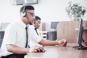 Operatore di assistenza clienti afroamericano con auricolare vivavoce che lavora in ufficio foto